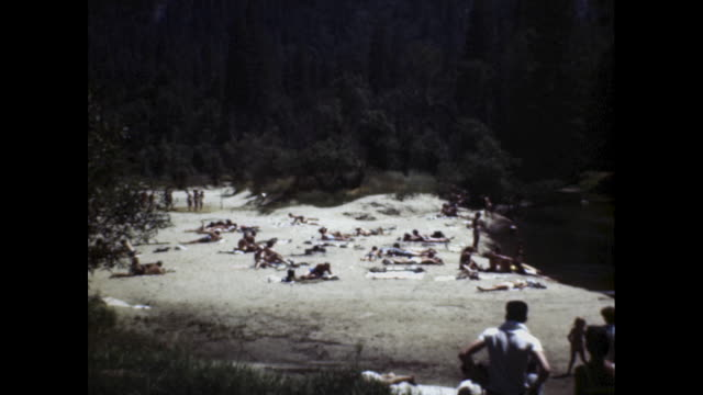 a long shot of a score of people lounging on a beach in san francisco - zurücklehnen stock-videos und b-roll-filmmaterial