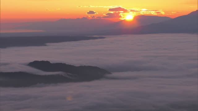 long shot of a sea of clouds over lake kussharo and sun rising from behind a mountain side - stratus stock videos & royalty-free footage