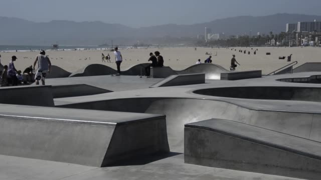 long shot of a skate park with skaters performing tricks world renowned venice beach is an ocean front community best known for its circuslike... - venice beach stock videos & royalty-free footage
