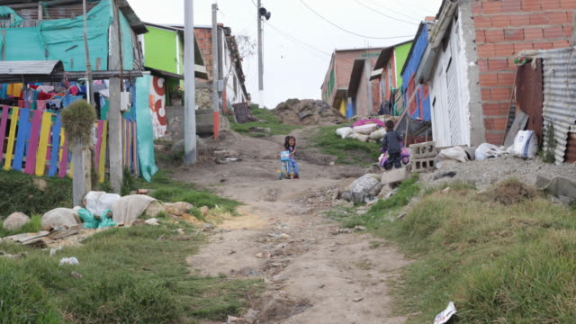 long shot of a slum in bogota showing a dirt road with little huts on the left and right side with small children a girl on a tricycle and a boy with... - america del sud video stock e b–roll