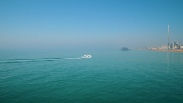 long shot of a speed boat travelling near brighton beach. - brighton england stock videos and b-roll footage