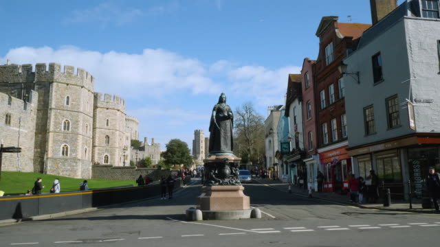 Long shot of a statue of Queen Victoria next to Windsor Castle.