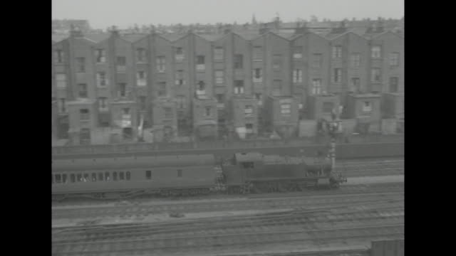 long shot of a steam train passing tenement buildings in london - steam train stock videos & royalty-free footage