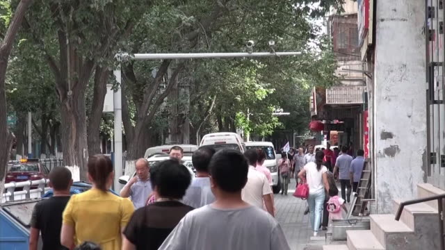 long shot of a street in urumqi where a surveillance camera is set on a pole above the street zooms in on the camera - xinjiang province stock videos & royalty-free footage
