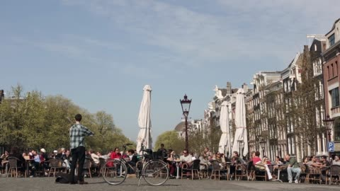 long shot of a street musician playing the violin at a square in amsterdam. general views of amsterdam on april 24, 2013 in amsterdam, netherlands - violin stock videos & royalty-free footage