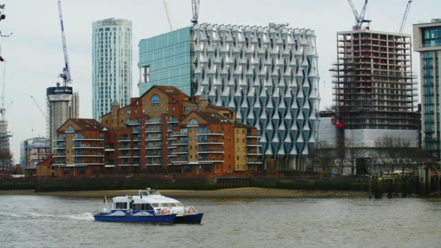 Long shot of a water clipper passing the new US embassy building at Nine Elms South London