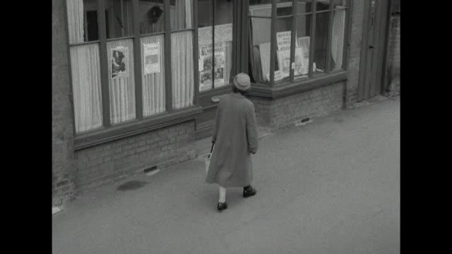 Long shot of a woman entering a citizen's advice office on a high street