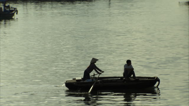 long shot of a woman rowing across ha long bay in a small boat. - halong bay stock videos and b-roll footage