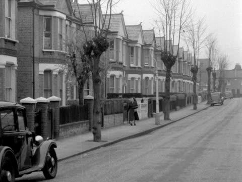 long shot of a woman walking along a typical suburban street 1957 - doppelhaus stock-videos und b-roll-filmmaterial