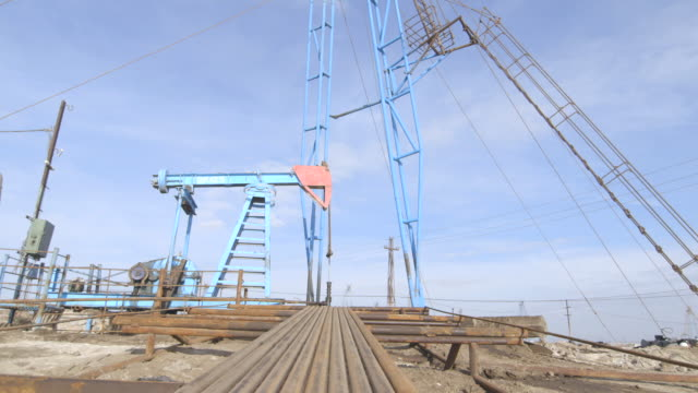 long shot of an operational pumpjack at an oil field near baku. - baku video stock e b–roll