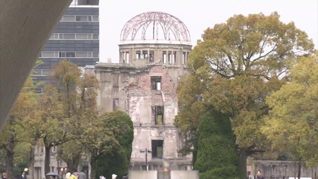 long shot of atomic bomb dome: pan from the dome to a stone monument located inside the memorial cenotaph. - armi di distruzione di massa video stock e b–roll
