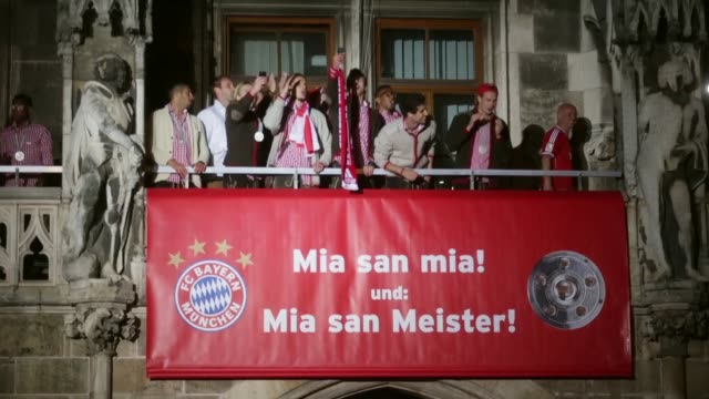 Long shot of Bayern Munich's Dante as he pours a glass of beer while celebrating the German championship title on the town hall balcony at...
