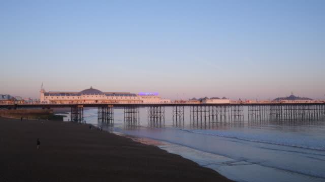 long shot of brighton's palace pier at dusk. - ブライトン パレスピア点の映像素材/bロール