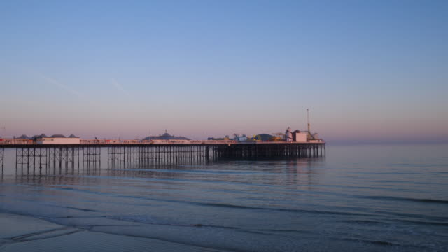 long shot of brighton's palace pier at dusk. - brighton brighton and hove stock-videos und b-roll-filmmaterial