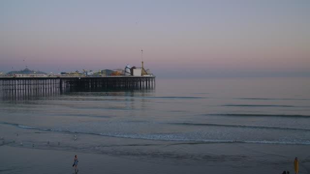 long shot of brighton's palace pier at dusk. - イーストサセックス点の映像素材/bロール