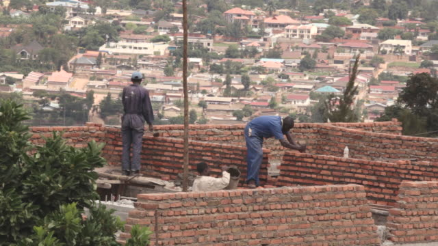 Long shot of builders laying bricks on a construction site in Kigali.