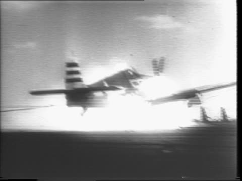 stockvideo's en b-roll-footage met long shot of carrier in water, black smoke billowing from it / us plane lands on carrier deck, bursts into flames / pilot climbing out of burning... - pilot