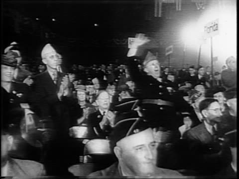 Long shot of convention hall / view of crowd standing and cheering / montage of close ups of Legionnaires in uniform / close up of convention sign...
