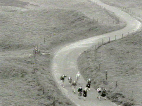 a long shot of female ramblers walking along a curved road in the peak district 1954 - winding road stock videos & royalty-free footage