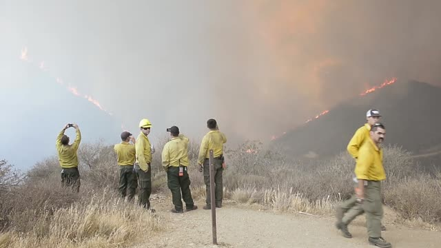 long shot of firefighter taking photographs of the burning hills hundreds of firefighters continue to battle wind and dry conditions with over 18000... - camarillo stock videos & royalty-free footage