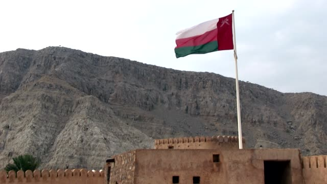 long shot of flag of the sultanate of oman over khasab city fortress - oman flag stock videos and b-roll footage