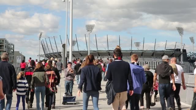 long shot of football fans arriving to attend the afl anzac day match between the essendon bombers and the collingwood magpies at the melbourne... - parade stock videos & royalty-free footage