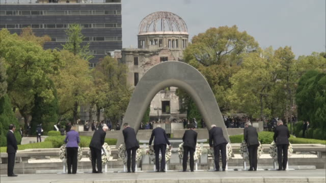 stockvideo's en b-roll-footage met long shot of g7 ministers laying wreaths to the memorial cenotaph in hiroshima peace memorial park viewed from behind - massavernietigingswapens