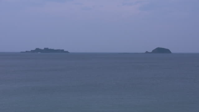 long shot of hashima island and nakanoshima island, nagasaki, japan - satoyama scenery stock videos and b-roll footage