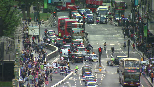 Long shot of heavy traffic and pedestrians near London's Westminster Bridge.