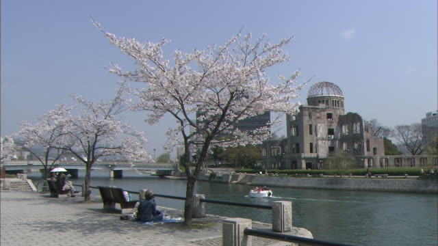 Long shot of Hiroshima Atomic Bomb Dome viewed from across Motoyasu River on a sunny day People having a picnic under a cherry blossom tree and a...
