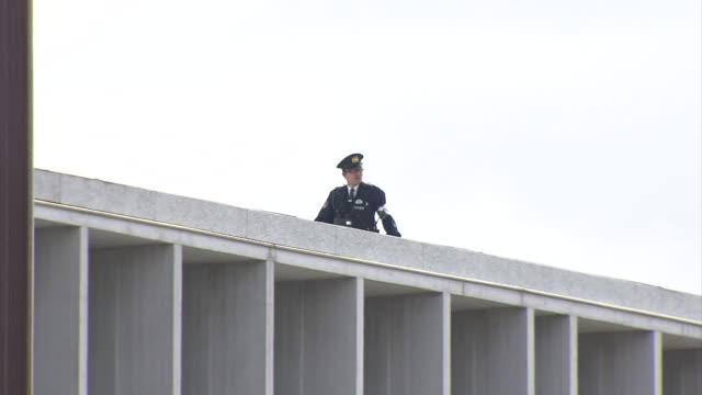 stockvideo's en b-roll-footage met long shot of hiroshima peace memorial museum zooming in on the rooftop where a police officer is carefully observing the area to maintain the... - massavernietigingswapens