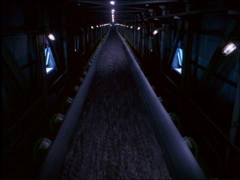 long shot of iron ore on conveyor belt in tunnel / Brazil