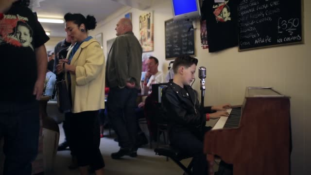 long shot of lewis jordan brown performing a rock n' roll song at the piano. fans of rock and roll, rockabilly, rockin' blues and americana gather at... - rocking video stock e b–roll