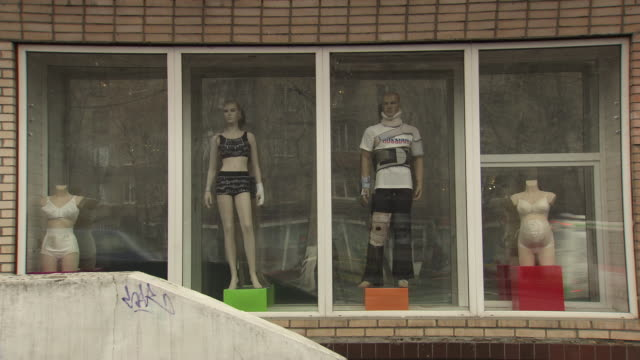 Long shot of mannequins wearing various support/underwear garments in a shop window. Moscow.