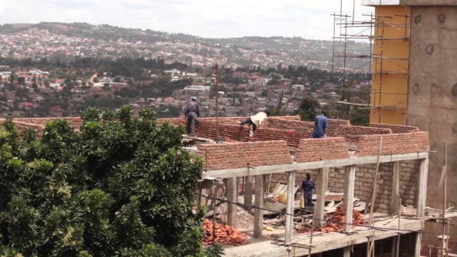 long shot of men working on a construction site in kigali. - ルワンダ点の映像素材/bロール
