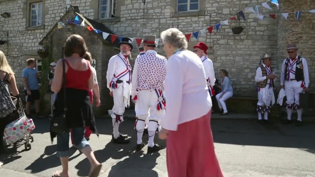 stockvideo's en b-roll-footage met long shot of morris men drinking and socializing outside the village pub. villagers celebrate traditional may bank holiday fayre on may 06, 2013 in... - festivalganger