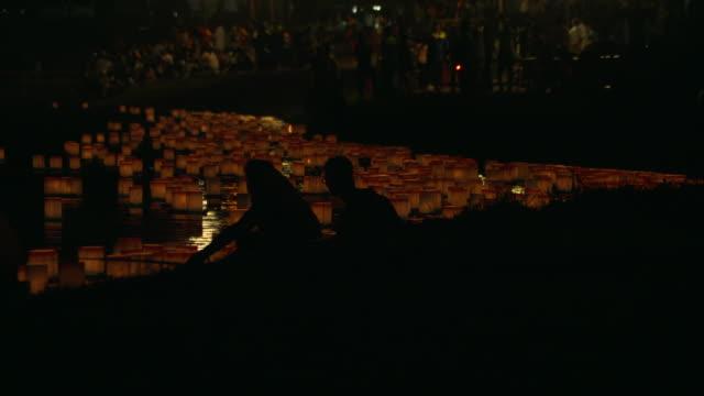 long shot of numerous orange-colored floating lanterns - paper lantern stock videos & royalty-free footage