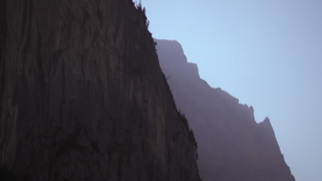 vidéos et rushes de long shot of paraglider falling off mountain - rock face