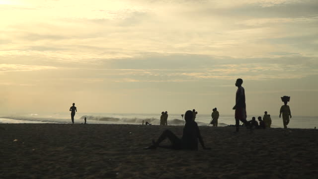 long shot of people relaxing on accra beach. - ghana stock videos & royalty-free footage