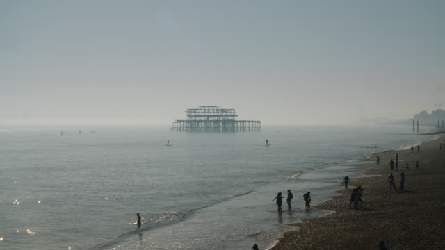 long shot of people relaxing on brighton beach, uk. - brighton brighton and hove stock-videos und b-roll-filmmaterial