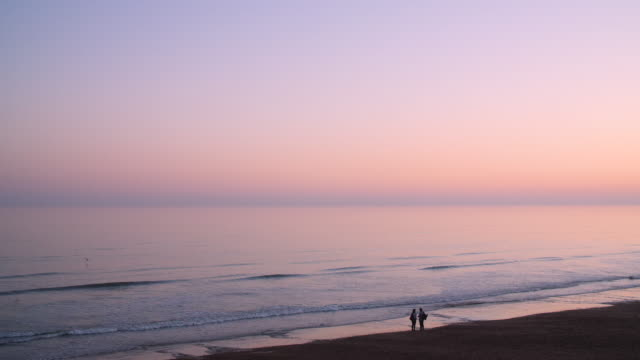 Long shot of people standing on the shoreline of Brighton beach at dusk.