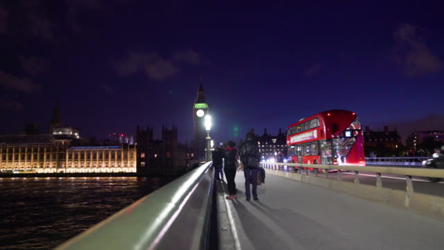 long shot of people standing on westminster bridge at night. - westminster bridge stock-videos und b-roll-filmmaterial