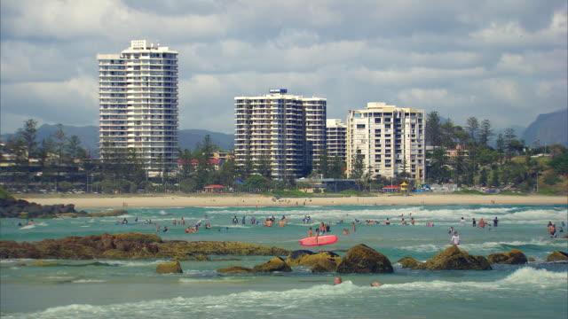 vídeos y material grabado en eventos de stock de long shot of people swimming and surfing at surfers paradise. - gold coast