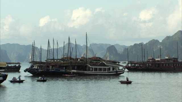 long shot of people using small boats to travel across ha long bay, vietnam. - halong bay stock videos and b-roll footage