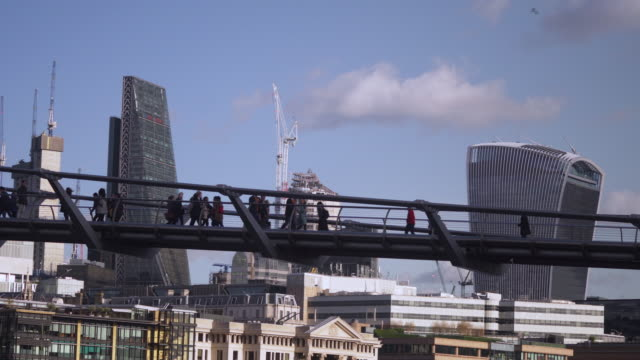 Long shot of people walking across London's Millennium Bridge with the 20 Fenchurch Street and 122 Leadenhall Street skyscrapers in the background.