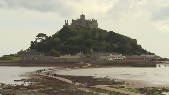 Long shot of people walking along a causeway to St Michael's Mount, Cornwall.