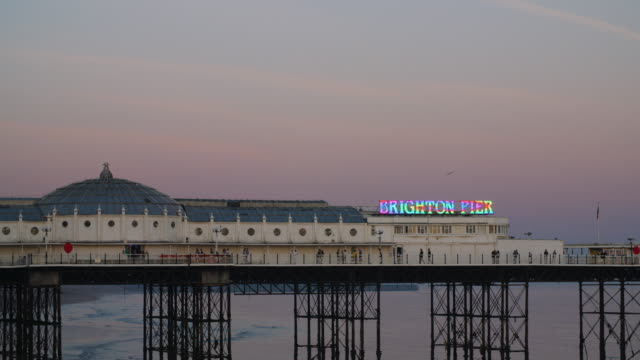 long shot of people walking along brighton's palace pier at dusk. - イーストサセックス点の映像素材/bロール