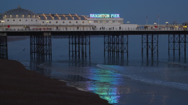 long shot of people walking along brighton's palace pier at dusk. - brighton england stock videos and b-roll footage