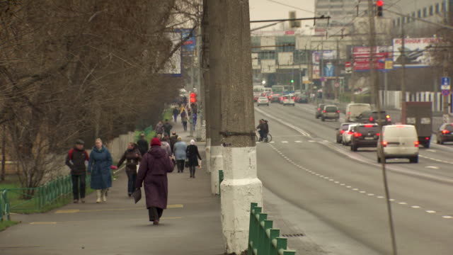 long shot of people walking down a busy road in moscow. - russland stock-videos und b-roll-filmmaterial