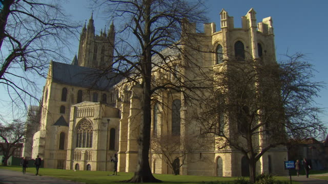 long shot of people walking past canterbury cathedral. - anglican stock videos & royalty-free footage